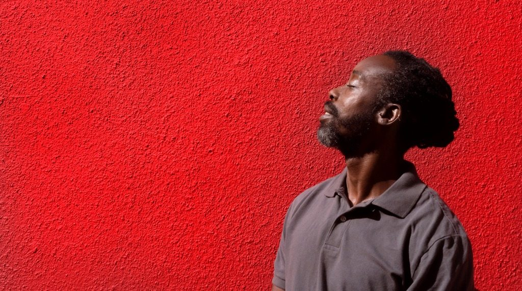 man breathing air in front of a wall